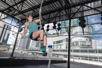 Woman training on exercise rope at rooftop gym in Bangkok