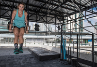 Woman training on exercise rings at rooftop gym in Bangkok