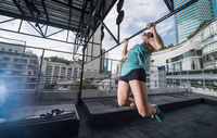 Woman training on exercise bar at rooftop gym in Bangkok