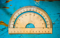 Overhead view of vintage protractor on blue table
