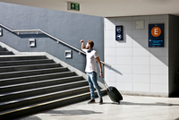 Young man with wheeled trolley bag, in front of steps in train station 11015303621| 写真素材・ストックフォト・画像・イラスト素材|アマナイメージズ