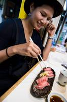 Woman eating sushi, Japan 11015303627| 写真素材・ストックフォト・画像・イラスト素材|アマナイメージズ
