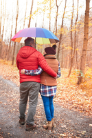 Couple walking along rural pathway, in autumn, carrying umbrella, rear view