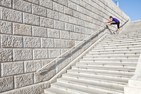 Young woman stretching leg at top of steps