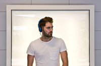 Young man wearing headphones, standing in front of illuminated screen