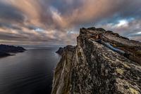 Woman looks out to sea from Segla Peak on Senja Island in autumn, Arctic Norway 11015303687| 写真素材・ストックフォト・画像・イラスト素材|アマナイメージズ