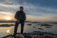 Man climbing a summit on Kvaloya Island in autumn, Arctic Norway 11015303693| 写真素材・ストックフォト・画像・イラスト素材|アマナイメージズ
