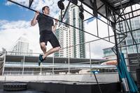 Man doing chin-ups in rooftop gym, Asok, Bangkok, Thailand 11015303705| 写真素材・ストックフォト・画像・イラスト素材|アマナイメージズ