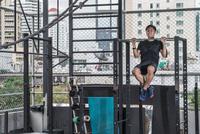 Man doing chin-ups in rooftop gym, Asok, Bangkok, Thailand 11015303712| 写真素材・ストックフォト・画像・イラスト素材|アマナイメージズ