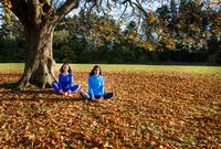 Two women doing yoga in park on autumn day 11015303735| 写真素材・ストックフォト・画像・イラスト素材|アマナイメージズ