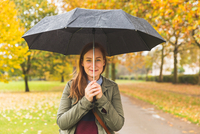 Portrait of young woman in park, holding umbrella