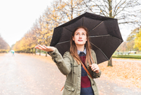 Young woman walking through park, carrying umbrella, hand out, checking for rain