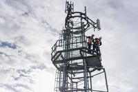 Engineers on the top of a transmission tower 11015303816| 写真素材・ストックフォト・画像・イラスト素材|アマナイメージズ
