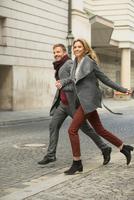 Mid adult couple running hand in hand on city street 11015303873| 写真素材・ストックフォト・画像・イラスト素材|アマナイメージズ