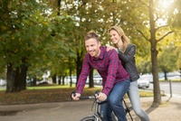 Romantic mid adult couple cycling in city park