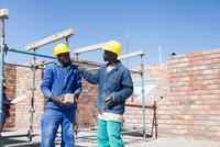 Builders talking on building site 11015303924| 写真素材・ストックフォト・画像・イラスト素材|アマナイメージズ