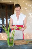 Woman scraping liquid from aloe leaf in handmade soap workshop 11015303996| 写真素材・ストックフォト・画像・イラスト素材|アマナイメージズ