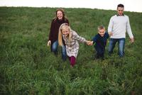Family holding hands walking in field 11015304079  写真素材・ストックフォト・画像・イラスト素材 アマナイメージズ