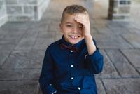 Portrait of boy shielding eyes looking at camera smiling 11015304081| 写真素材・ストックフォト・画像・イラスト素材|アマナイメージズ
