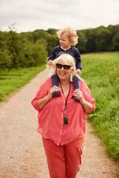Grandmother carrying grandson on shoulders 11015304100| 写真素材・ストックフォト・画像・イラスト素材|アマナイメージズ
