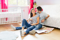Pregnant couple sitting on floor in nursery holding scan smiling