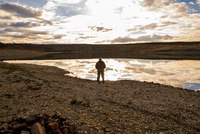 Man viewing landscape from water's edge, Ural, Russia
