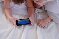 Children playing game on mobile phone in bed 11015304230| 写真素材・ストックフォト・画像・イラスト素材|アマナイメージズ