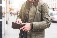 Man checking wallet in front of shop, London, UK 11015304240| 写真素材・ストックフォト・画像・イラスト素材|アマナイメージズ