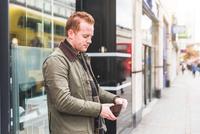 Man checking wallet in front of shop, London, UK 11015304241| 写真素材・ストックフォト・画像・イラスト素材|アマナイメージズ