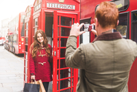 Couple taking photograph by telephone booth, London, UK 11015304242| 写真素材・ストックフォト・画像・イラスト素材|アマナイメージズ