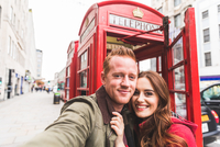 Couple taking selfie by telephone booth, London, UK 11015304243| 写真素材・ストックフォト・画像・イラスト素材|アマナイメージズ