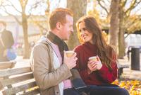 Couple having coffee on park bench, London, UK 11015304273| 写真素材・ストックフォト・画像・イラスト素材|アマナイメージズ