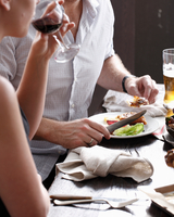 Two people eating and drinking in restaurant, mid section