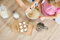 Mother helping daughter whisk ingredients together in bowl, overhead view