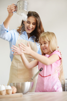 Mother and daughter baking together, sieving flour, fooling around