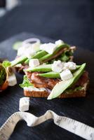 Meat, feta and avocado open sandwiches on slate 11015304482| 写真素材・ストックフォト・画像・イラスト素材|アマナイメージズ