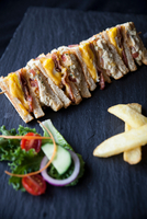 Row of sandwiches with chips and salad on slate 11015304487| 写真素材・ストックフォト・画像・イラスト素材|アマナイメージズ
