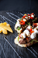 Meat, feta and tomato open sandwiches with chips and sauce garnish on slate 11015304489| 写真素材・ストックフォト・画像・イラスト素材|アマナイメージズ
