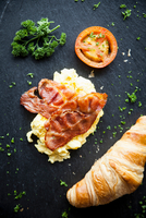 Overhead view of croissant with bacon, omelette and tomato breakfast on slate