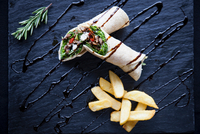 Overhead view of tortilla wraps with chips and sauce garnish on slate 11015304501| 写真素材・ストックフォト・画像・イラスト素材|アマナイメージズ
