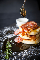Breakfast bacon crumpet with maple syrup pouring from spoon onto slate 11015304504| 写真素材・ストックフォト・画像・イラスト素材|アマナイメージズ