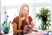 Businesswoman having coffee break texting on smartphone in office 11015304522| 写真素材・ストックフォト・画像・イラスト素材|アマナイメージズ