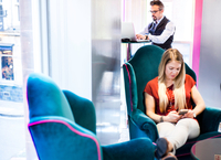 Businessman using laptop whilst client in office armchair texting on smartphone 11015304523| 写真素材・ストックフォト・画像・イラスト素材|アマナイメージズ