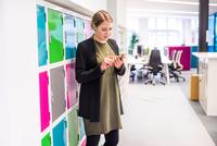 Businesswoman texting on smartphone in office 11015304526| 写真素材・ストックフォト・画像・イラスト素材|アマナイメージズ