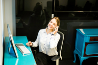 Businesswoman talking on smartphone at office desk 11015304527| 写真素材・ストックフォト・画像・イラスト素材|アマナイメージズ