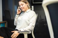Businesswoman talking on smartphone at office desk 11015304528| 写真素材・ストックフォト・画像・イラスト素材|アマナイメージズ