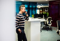 Businessman working late in office making smartphone call