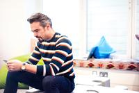 Businessman sitting in office reading smartphone texts 11015304531| 写真素材・ストックフォト・画像・イラスト素材|アマナイメージズ