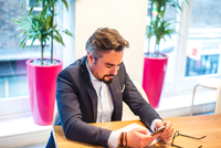 Businessman at office desk reading smartphone texts