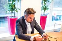Businessman at office desk reading smartphone texts 11015304532| 写真素材・ストックフォト・画像・イラスト素材|アマナイメージズ